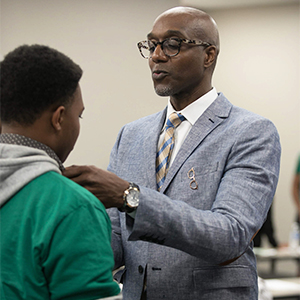 Stylist Jeff McAlister knots a tie for a participant of the African American Male Initiative Summer Institute at Concordia.