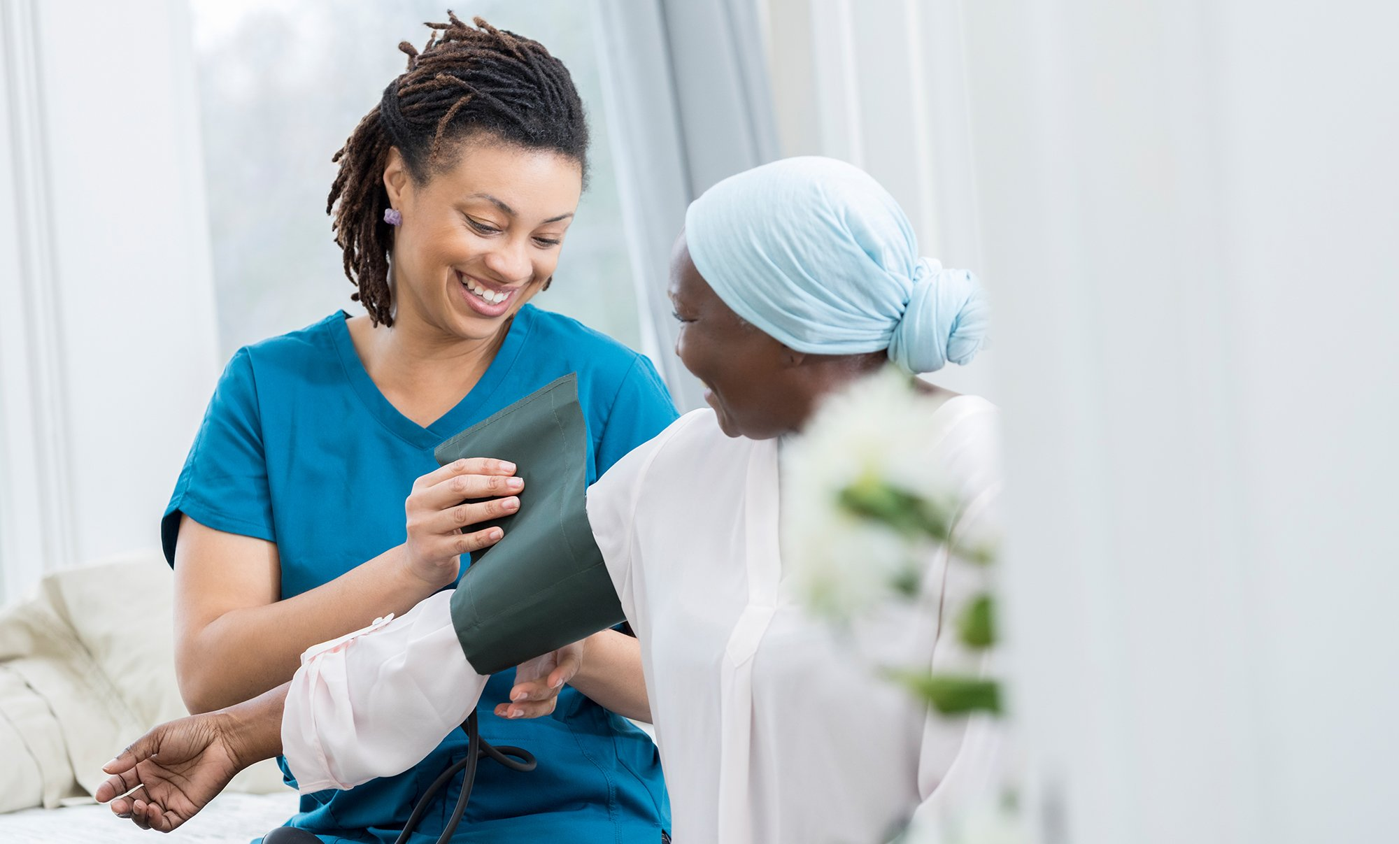 Nurse caring for a patient by taking blood pressure