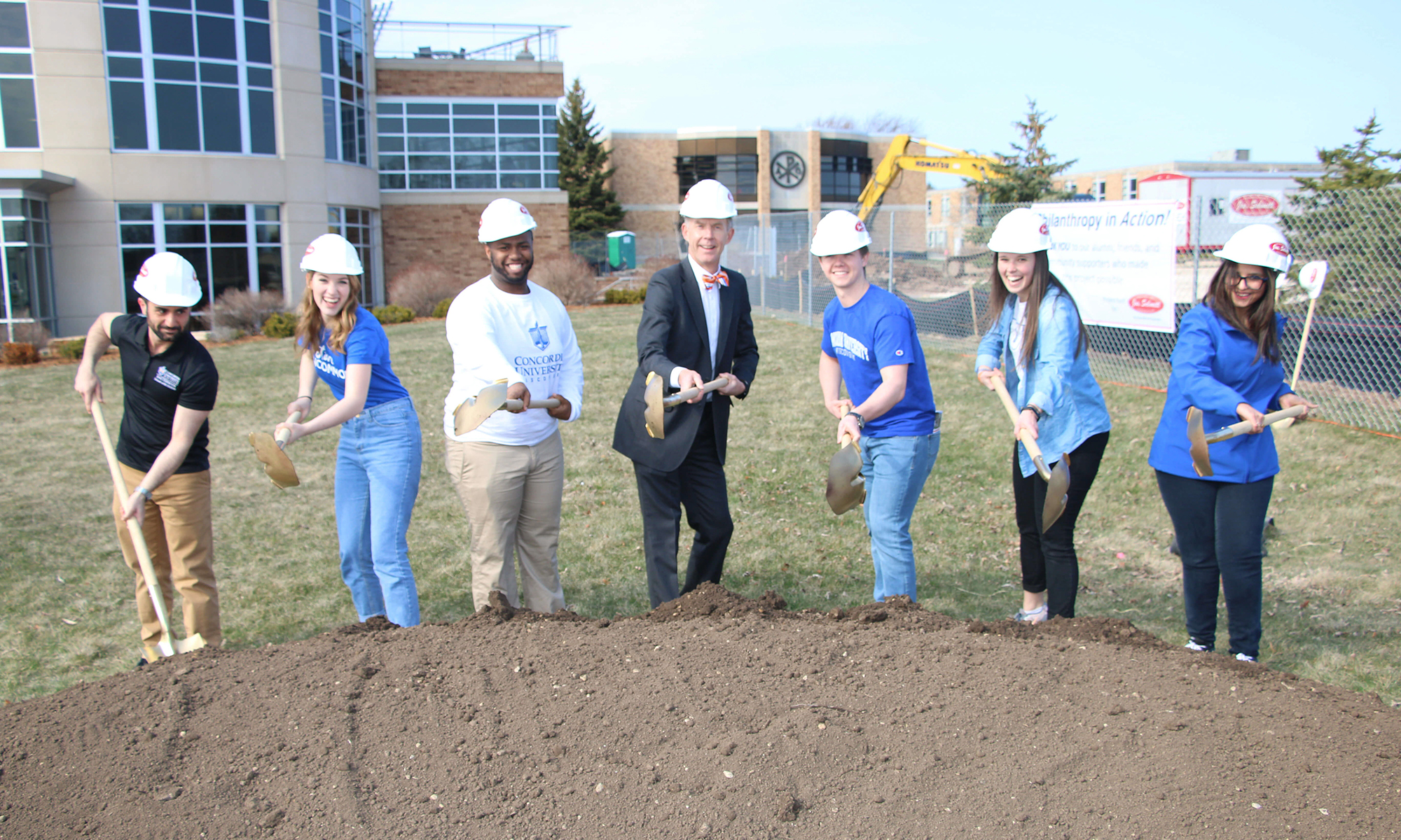 Students help President Ferry ceremoniously shovel the dirt for the new academic building.