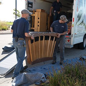 Maintenance workers haul the parts of the practice organ off the U-Haul on the Mequon campus.