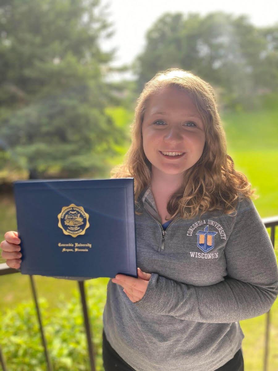 Jen Sheridan holding diploma after graduation