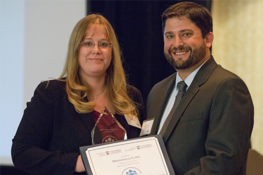 Andy Traynor [right], PharmD, chair and associate professor of pharmacy practice at Concordia, hands Dr. Sarah Rall [left], director of pharmacy, Marshfield Clinic a CMMA certificate.