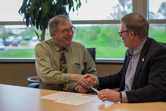 Senior VP of Academics Dr. William Cario shakes hands with Edgewood College Vice President of Academic Affairs Dr. Dean Pribbenow after a May 23 signing agreement.
