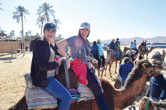 From the Dead Sea to the desert, Monica Lee and Mackenzie Divine are ready for the camel caravan to move. Photo Credit: Mackenzie Drinan.